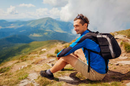 Trip to Carpathian mountains. Happy man hiker with backpack resting on top of Hoverla enjoying landscape. Traveling tourism in summer Ukraine