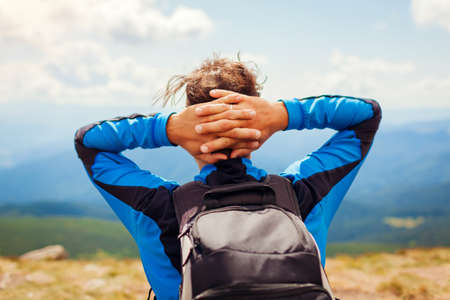 Trip to Carpathian mountains in summer. Happy man hiker with backpack resting on top of Hoverla enjoying landscape. Back view of traveler. Eco tourism