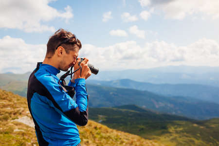 Photographer taking pictures of Carpathian mountains landscape on top of Hoverla. Man hiker using camera to make photos and footage. Traveling wtih digital devices Archivio Fotografico