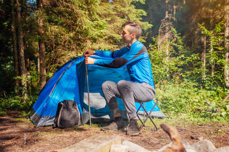 Young man setting up tent on camping trip in forest. Summer camping with campfire. Traveler adjusting tent elements. Archivio Fotografico