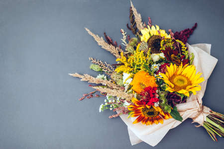 Fall bouquet of yellow red orange flowers wrapped in paper and arranged on grey background. Sunflowers, amaranth, daisies with zinnias and grasses