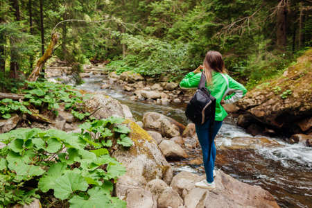 Traveler hiker with backpack enjoys landscape by mountain river in Carpathian forest. Woman tourist enjoys view. Trip to summer Ukraine