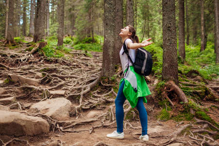 Woman hiker walking through mountain forest path surrounded with roots in Carpathians. Traveler with backpack feels happy. Trip to summer Ukraine Foto de archivo