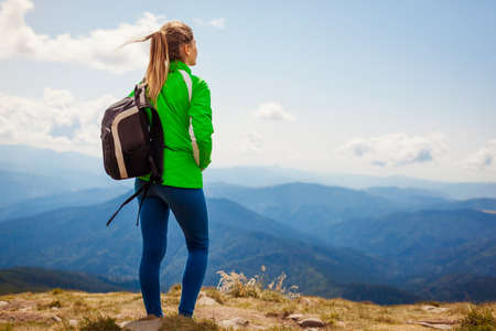 Trip to Carpathian mountains. Happy woman tourist hiker with backpack admires view on top of Hoverla enjoying landscape and fresh air. Traveling in summer Ukraine