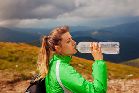 Sportive young woman hiker drinks water while climbing on Hoverla mountain in Carpathians. Tired traveler with backpack resting. Trip to summer Ukraine Archivio Fotografico