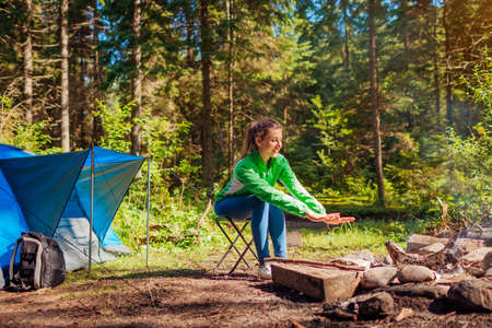 Woman relaxing by campfire in forest sitting next to tent warming hands. Summer camping. Traveling alone enjoying nature Archivio Fotografico