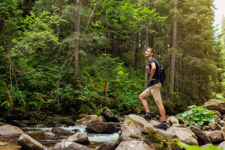 Traveler hiker with backpack enjoys landscape by mountain river in Carpathian forest. Trip to summer Ukraine. Sportive active lifestyle