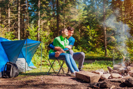 Young couple of travelers enjoy campfire in summer forest. Tourists sitting by tent hugging. Camping in woods
