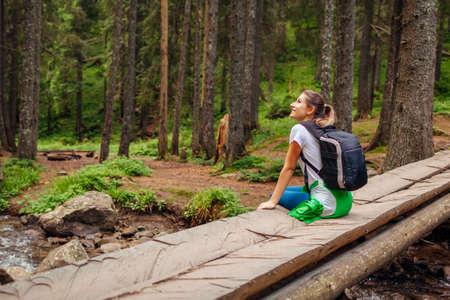Traveler hiker with backpack sitting on bridge across river in Carpathian forest resting. Trip to summer Ukraine. Woman tourist enjoying natural landscape.