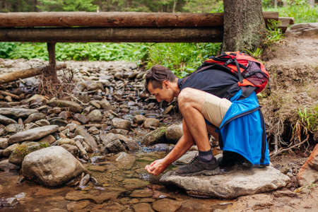Traveler hiker with backpack wants to drink water and wash face in mountain river in Carpathian forest by bridge. Tourist having rest by stream