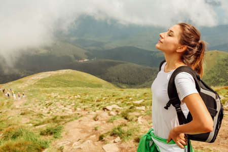 Woman hiker resting after climbing on mountain surrounded with clouds in Carpathians. Traveler with backpack breathing. Trip to summer Ukraine