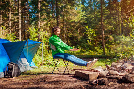 Woman relaxing by campfire in forest sitting next to tent warming hands and feet. Summer camping. Traveling alone enjoying nature Foto de archivo