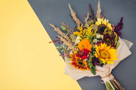 Fall bouquet of yellow red orange flowers wrapped in paper and arranged on brown background. Sunflowers, amaranth, daisies with zinnias and grasses
