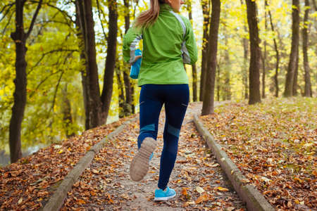 Runner working out in autumn park wearing sportive clothes. Young woman running with water bottle among yellow trees. Close up of shoes