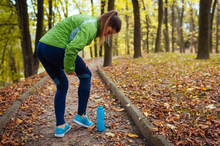 Runner injured leg during intense training in autumn park. Woman feels hip pain holding it with hand. Workout hurt