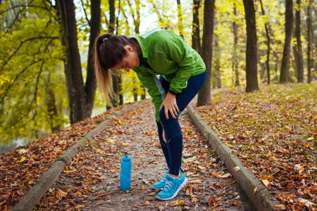 Runner injured leg during intense training in autumn park. Woman feels knee pain. Workout hurt