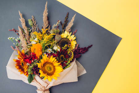 Fall bouquet of yellow red orange flowers wrapped in paper and arranged on grey and yellow background. Sunflowers, amaranth, daisies with zinnias and grasses Foto de archivo