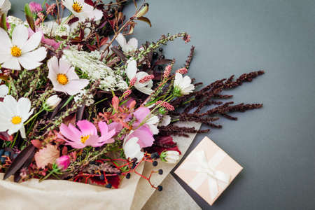 Fresh bouquet of white pink flowers with burgundy foliage wrapped in paper and arranged on grey background with gift box. Present for holiday