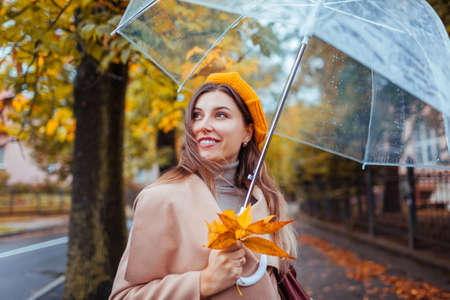 Happy young woman walking outdoors under transparent umbrella during rain holding yellow leaves. Stylish girl wearing fashionable clothes and accessories. Fall season Foto de archivo