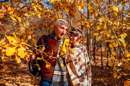 Fall season. Senior family couple walking in autumn park. Happy middle-aged man and woman hugging and relaxing outdoors.