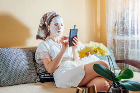 Woman with facial sheet mask applied relaxing at home after bath sitting on couch using smartphone. Skincare routine