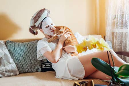 Woman with facial sheet mask applied relaxing at home after bath playing with cat. Enjoying time with pet. Self care routine Foto de archivo