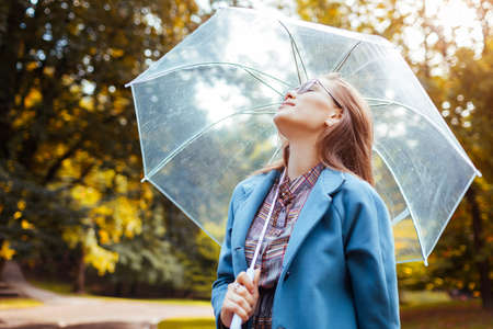 Outdoor portrait of stylish woman walking in park with transparent umbrella breathing. Autumn fashionable accessories