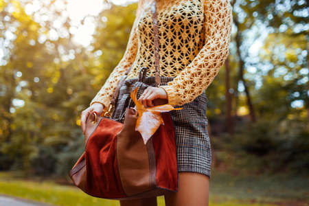 Close up of female leather handbag. Woman holds brown orange purse in park with yellow leaves. Stylish trendy accessories