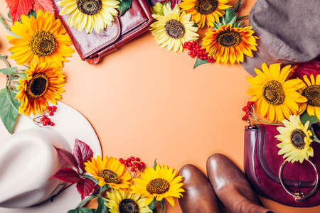 Autumn fall female fashion in orange yellow red colors with sunflowers. Set of clothes shoes accessories. Copy space. Sale and shopping concept Foto de archivo