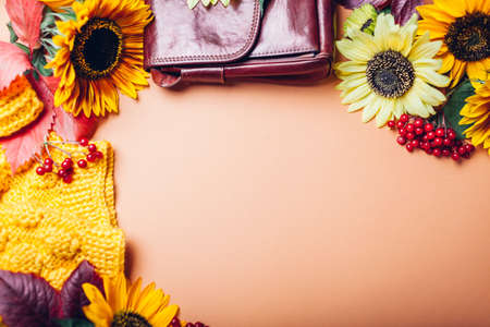 Autumn fall female fashion in orange yellow red colors with sunflowers. Sweater with burgundy handbag. Clothes and accessories. Sale and shopping Foto de archivo