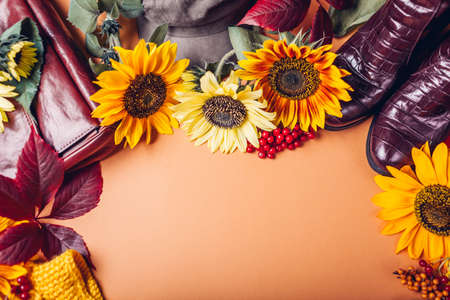 Top view of autumn fall female fashion in orange yellow red colors with flowers. Clothes shoes accessories. Sale and shopping concept