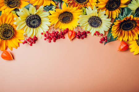 Fall autumn floral background. Bunch of yellow orange lime sunflowers with red berries and seedpods. Space
