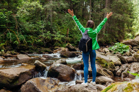 Traveler hiker with backpack raising arms by mountain river waterfall in Carpathian forest feeling happy. Woman tourist enjoys landscape. Trip to summer Ukraine