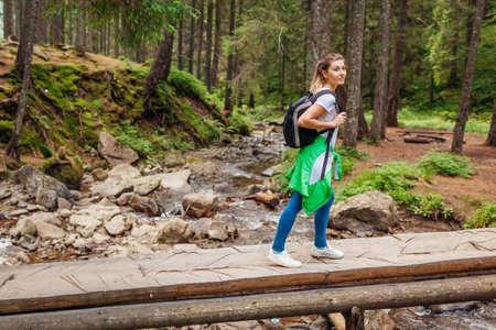Traveler hiker with backpack crossing mountain river in Carpathian forest walking on wooden bridge. Woman tourist enjoying natural landscape. Trip to summer Ukraine