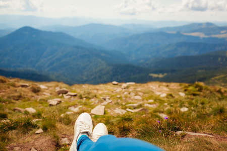 Hiking in Carpathian mountains. Hiker woman relaxing enjoying landscape lying on grass. Traveling in summer Ukraine. Close up of shoes