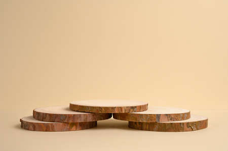 Wooden podium on beige background for product. Front view. Copy space.