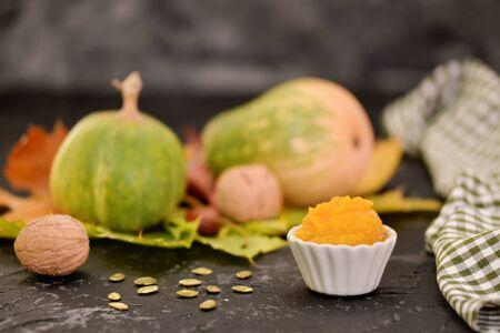 Fresh homemade vegan pumpkin puree or mash in small bowl, among autumn attributes:walnut, yellow leaves, pumpkin and pumpkins seeds