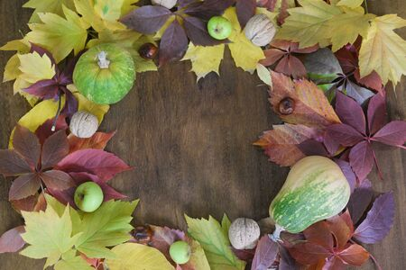 Pumpkin, apples and walnuts on a wooden table with autumn yellow leaves