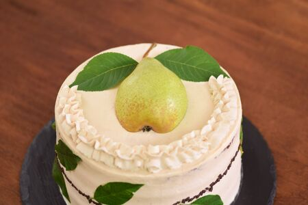 Cream cake with decorated with fresh pear and green leaves