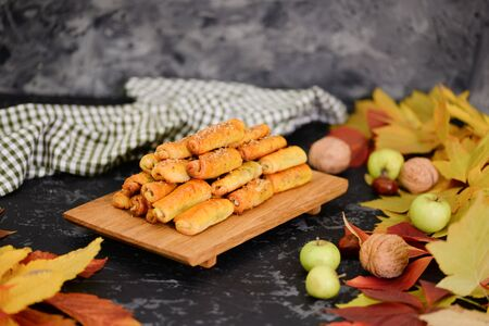 Delicious homemade cookies with apples and walnuts. Sweet pastries with an autumn theme and autumn yellow leaves. Autumn appetizing background.