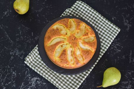 Homemade pear pie on a black table with pears in the background