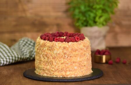 Delicious homemade Napoleon layered cake with raspberries on a wooden table