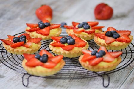 Summer berry tartlets with cream and fresh berries. Healthy summer pastry dessert for party