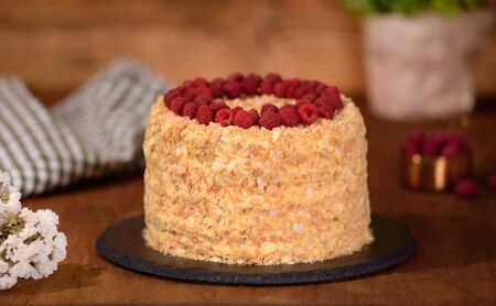 Napoleon layered cake with berries on a wooden table