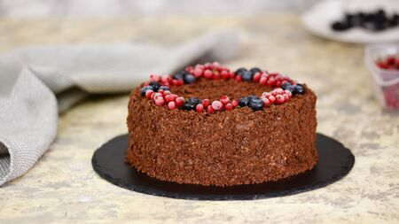 Russian chocolate cake Napoleon with berries and sprinkled with crumbs