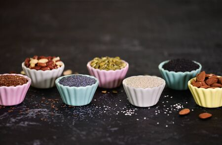 Assortment of nuts and seeds in small bowls on a black background