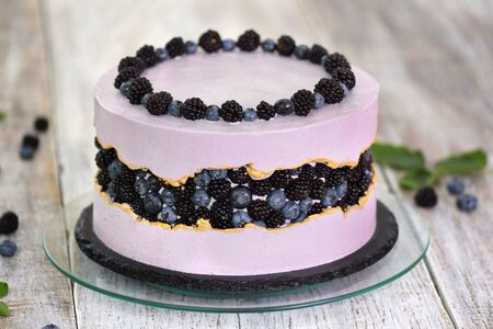 Purple beautiful cake decorated with berries, blackberries and blueberries. Concept delicate dessert holiday table Stok Fotoğraf