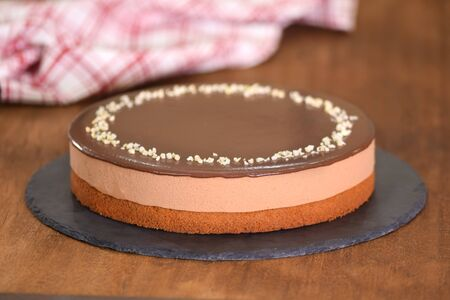 Delicious chocolate mousse cake decorate with nuts on the top.
