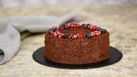 Russian chocolate cake Napoleon with berries and sprinkled with crumbs.
