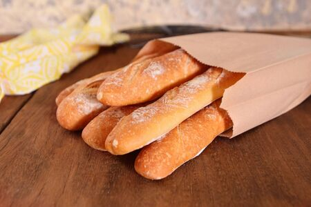French baguettes in paper bags on wooden background.